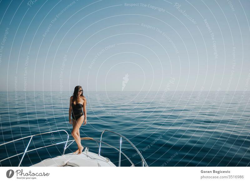 Junge Frau in Badebekleidung steht an der Vorderseite einer Yacht Erwachsener attraktiv schön Schönheit Bikini blau Boot Bootfahren Körper brünett Kaukasier