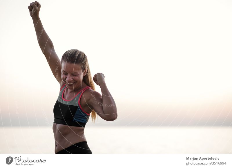 Junge Frau steht mit erhobenen Armen triumphierend am Meer Errungenschaft Aktion aktiv Aktivität Waffen Athlet schön Herausforderung Ausdauer Abend Übung passen