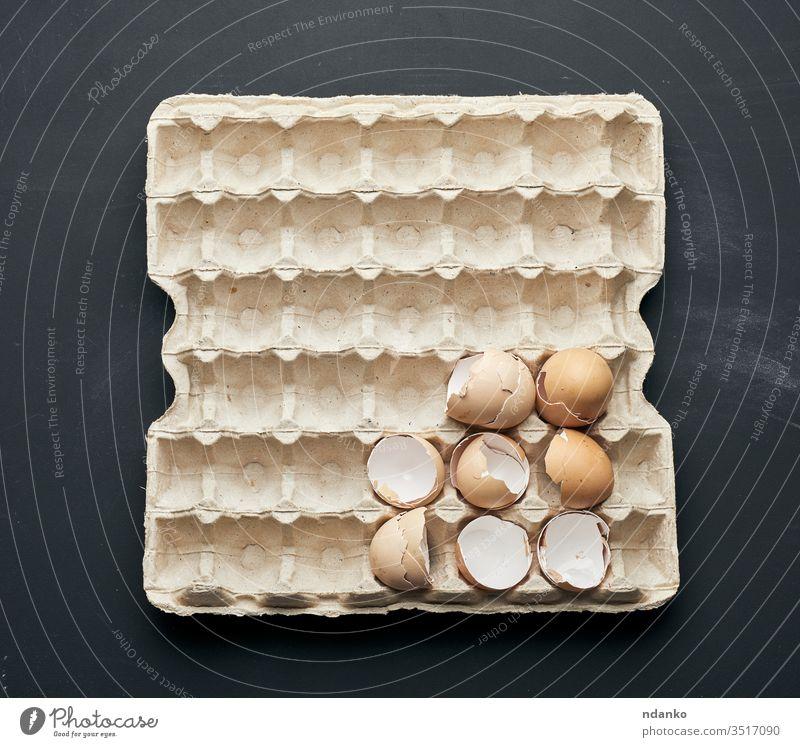 Eierschale in einem Papiertablett auf einem schwarzen Holztisch Bauernhof Feder Lebensmittel Zerbrechlichkeit gebrochen Hintergrund Vogel Holzplatte Frühstück
