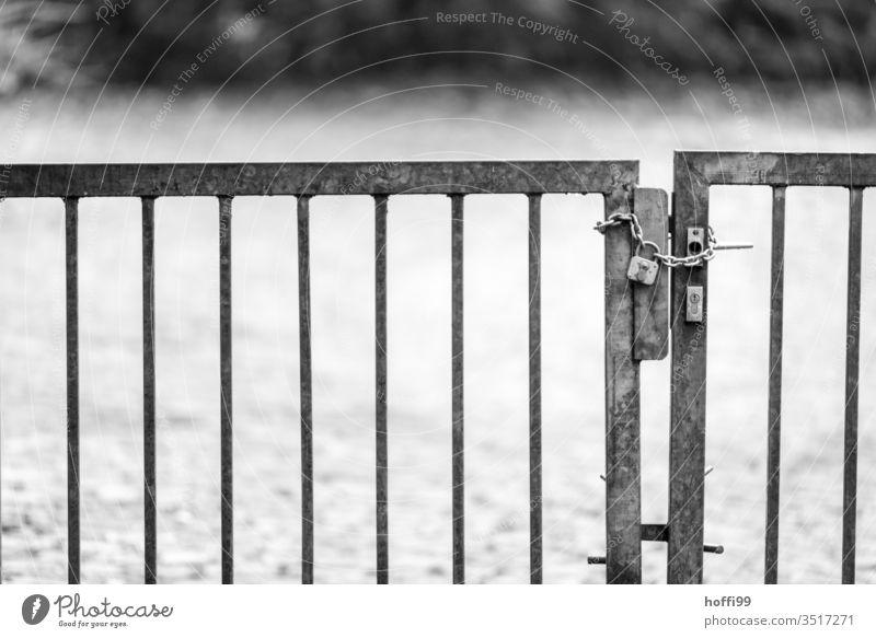 die Kette mit Schloss am Zaun schließt sicher die Tür des Tores geschlossen abgeschlossen abgeschlossener Garten Park Spielplatz Sicherheit Eingang Griff alt