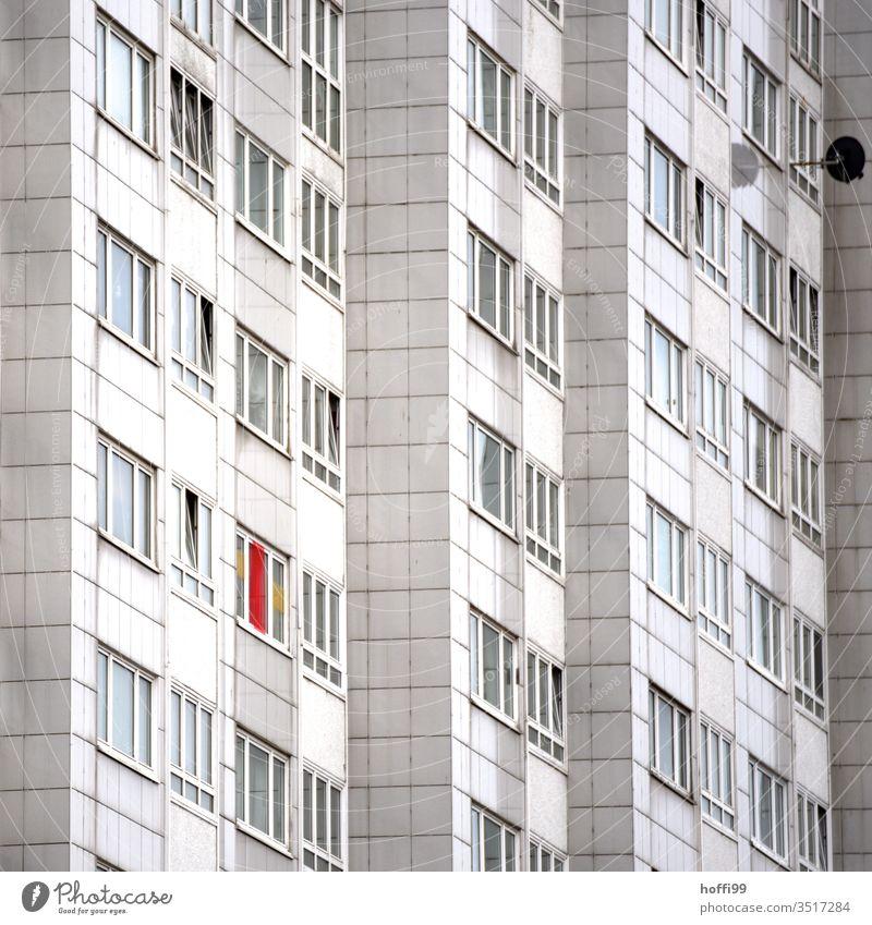 runtergekommene Aussenfassade eines Wohnhauses Haus Balkon Fahne bedrohlich Kontrast Klischee trocken hässlich Zukunftsangst Stress dreckig Fenster Wand Mauer