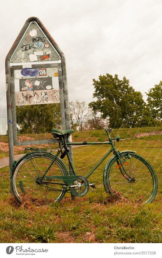 grünes Fahrrad angeschlossen an einem Schild Verkehrsschild Wiese abgestellt einsam Außenaufnahme Farbfoto Menschenleer Hinweisschild Sicherheit