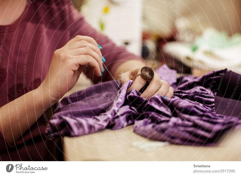 Weibliche Hände nähen Stoff mit der Nadel am Arbeitsplatz der Näherin. Seitenansicht Nadelbett Helfer Ring Faser Stickereien Kreide Schneiden Briefpapiermesser