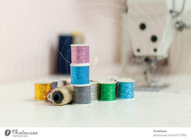 Nähzubehör auf dem Schreibtisch in Nahaufnahme. Nähgarne aus Lurex in Spulen, im Hintergrund eine Nähmaschine Faser Kreide Tisch Nähset Rolle Kulisse rot gelb