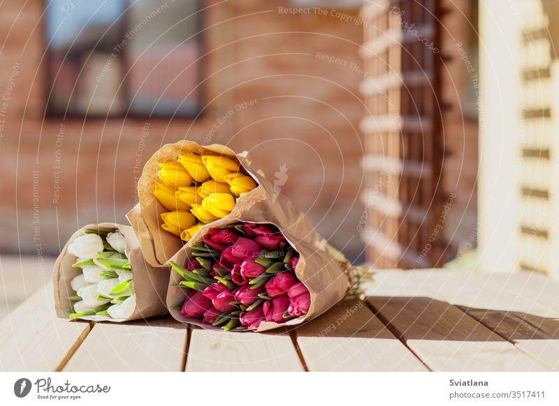 Schöne bunte Tulpensträuße aus Bastelpapier liegen auf der Straße auf einem Holztisch. Seitenansicht Markt Blume Blumenstrauß Frühling rot rosa März