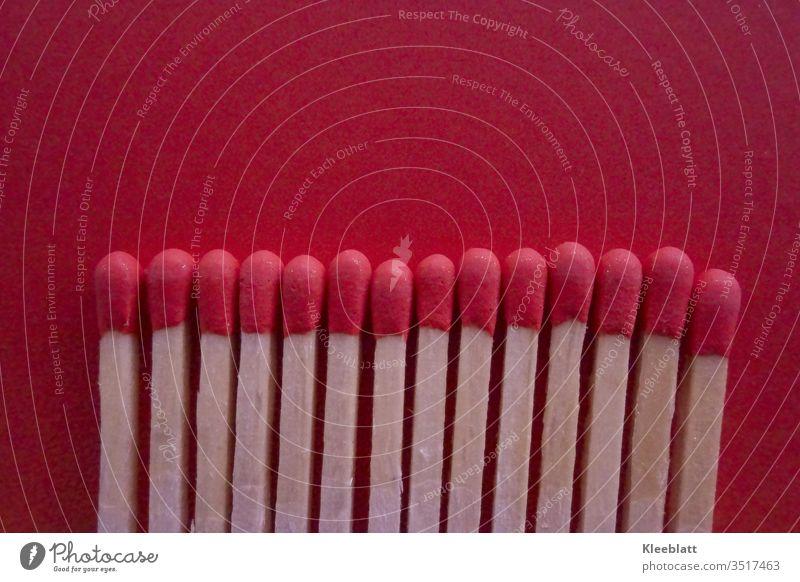 Streichhölzer auf rotem Hintergrund Streichholz anzünden Feuer streicholzköpfe Brandgefahr Flamme heiß Rauch bedrohlich Licht gefährlich Innenaufnahme Farbfoto