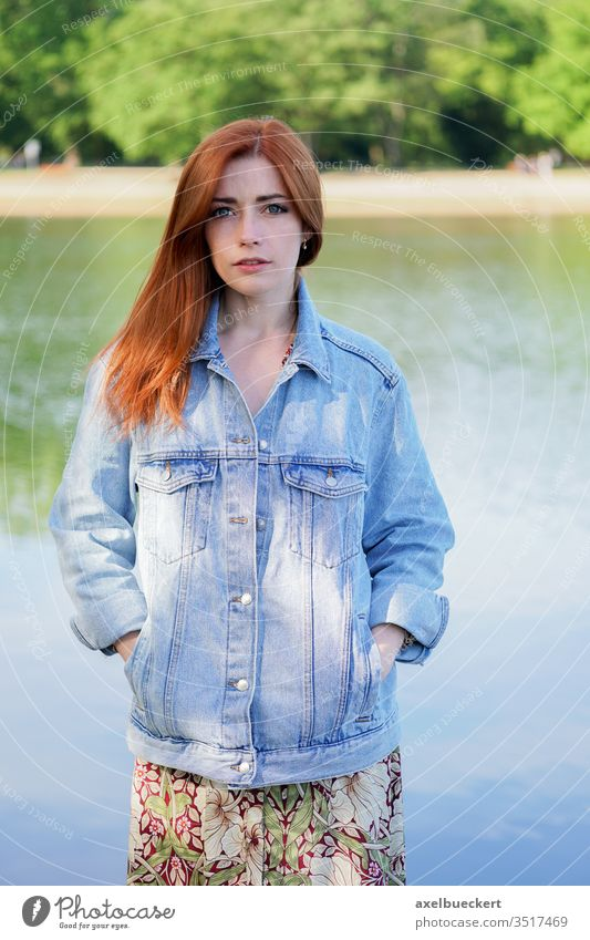 authentische junge Frau in Jeansjacke über Sommerkleid am See stehend Mädchen Jeanshose Jeansstoff Jacke Erwachsener Person Menschen Frauen rote Haare Rotschopf