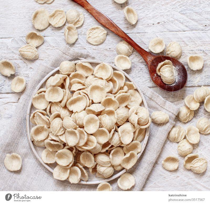 Frische rohe italienische Teigwaren Orecchiette Apulien Spätzle Italienisch frisch trocknen traditionell Bestandteil Draufsicht Messer dunkel Teller Diät Mehl