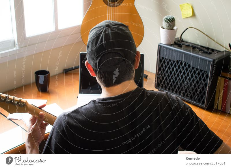Junger Musiker in Mütze, der zu Hause am Computer das Gitarrenspiel lernt. Konzept des Erlernens von Musik mit Online-Unterricht unter Verwendung von Technologie.