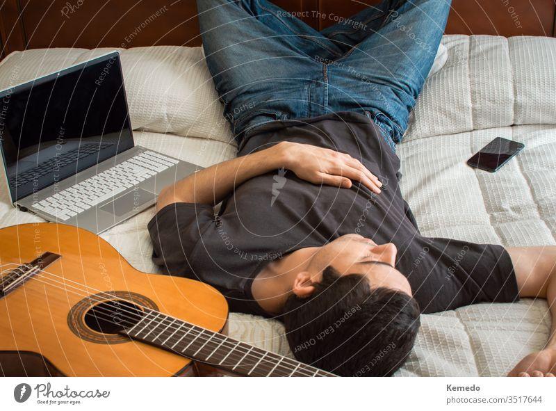 Gelangweilter Mann schläft in einem großen Bett, nachdem er Gitarre gespielt und einen Laptop benutzt hat, um sich zu beschäftigen. Konzept, Zeit zu Hause mit Musik und Technik zu verbringen.