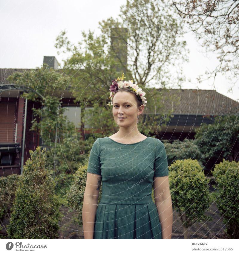 Analoges Portrait einer jungen Frau mit Blumenkranz im Garten schön sportlich schlank Schaukel grün Pflanze Hecke Stäucher Baum Natur Gartenfee Farbfoto