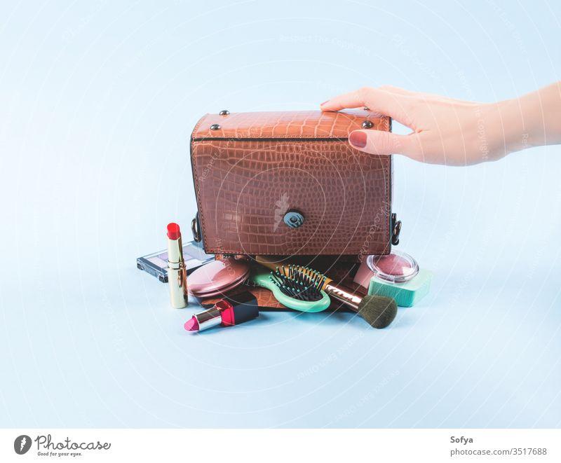 Damenhandtasche umgedreht mit Schminkutensilien Mode Frau Schönheit zusammenstellen kaufen Hand organisieren Zubehör Orden Sauberkeit Lippenstift Bürste