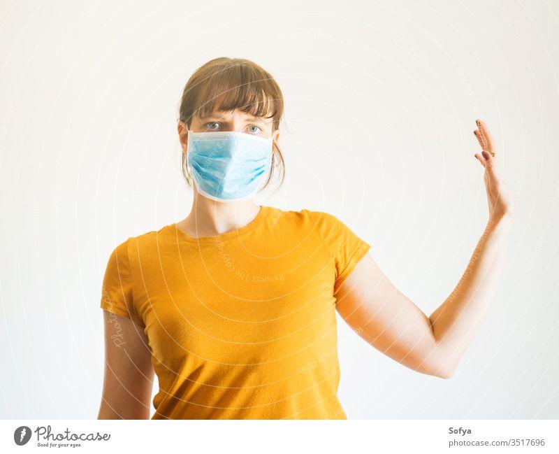 Junge Frau in Gesichtsmaske mit erhobenem Arm Coronavirus Mundschutz soziale Distanzierung Quarantäne Hand stoppen vereinzelt COVID19 entfernt zu Hause bleiben