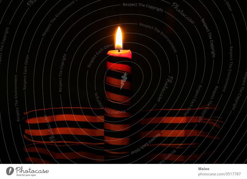Brennende Gedächtniskerze eingewickelt in ein George-Band Hintergrund Bändchen Symbol Nahaufnahme Licht Kerze Feiertag usr altehrwürdig Mut