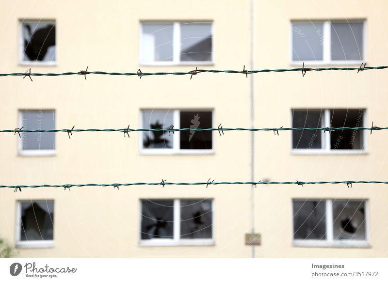 Reihen von Stacheldraht im Hintergrund ein verlassenes Wohngebäude mit zerbrochenen Fenstern. Konzept von Geisterstadt, Isolation und Sicherheit. Gefängnis, Flüchtling, Einsamkeit