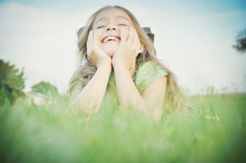 mächen liegt auf aufgestützten armen im gras und lacht Kind Mädchen Kindheit Freude lachen Lebensfreude Spaß Leichtigkeit Gesicht Hände Gras liegen Lächeln