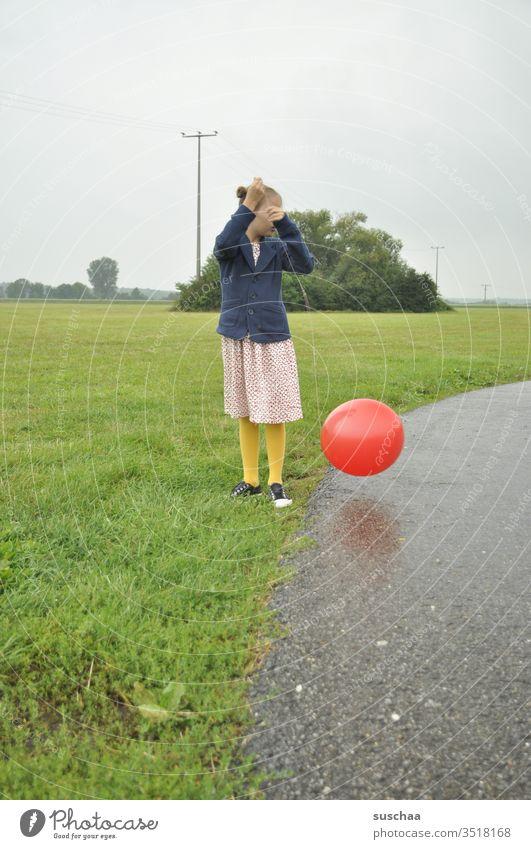 altmodisch gekleidetes mädchen spielt mit einem roten luftballon Mädchen Kind draußen Weg Wiese Gras Feld Luftballon roter Luftballon Ball rund spielen Umwelt