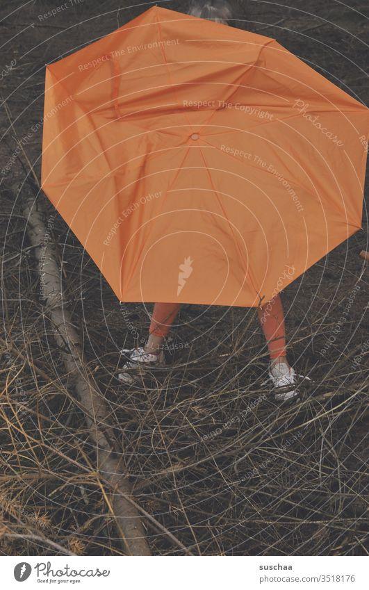 kind versteckt sich hinter einem kaputten orangefarbenen regenschirm im wald und nur die füße gucken raus .. Kind Beine Füße Regenschirm Ast Baum Wald Zweige