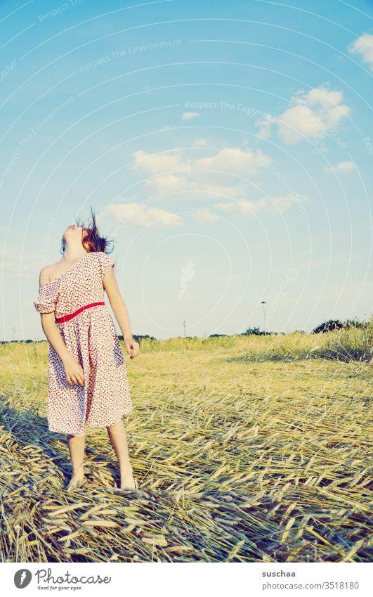 mädchen steht auf einem kornfeld im sommer und wirft den kopf übermütig nach hinten .. Kind Mädchen Sommer Strohfeld Getreidefeld Sommerkleid frei Freude