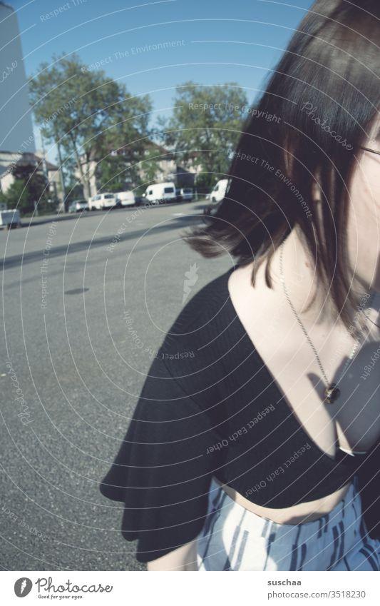jugendliche läuft aus dem bild Jugendliche Teenager seitlich dran vorbei aus dem Bild Dekolleté Halskette Straße Asphalt Parkplatz Außenaufnahme Stadt