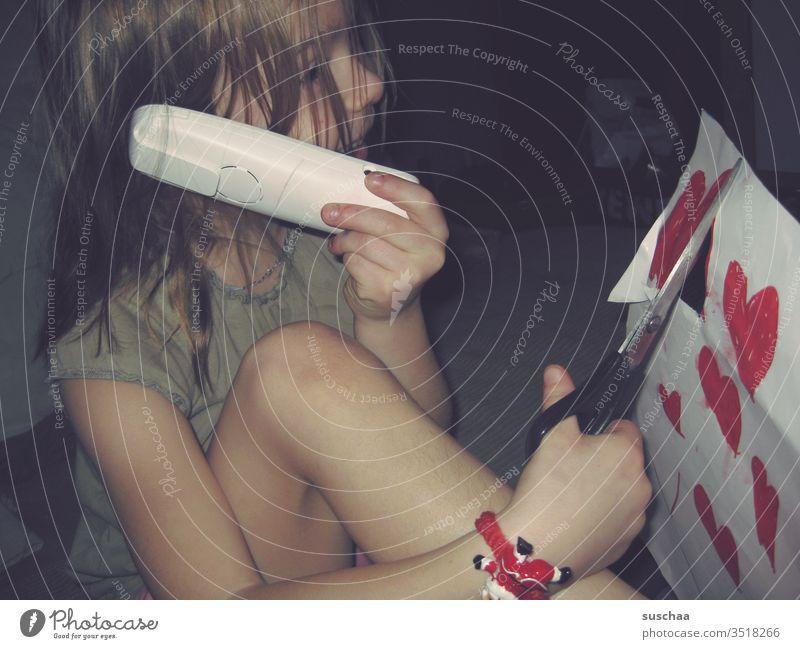 multitasking | mädchen telefoniert und schneidet gleichzeitig herzchen aus Kind Kindheit Multitasking Mädchen witzig geschickt Geschicklichkeit Telefon