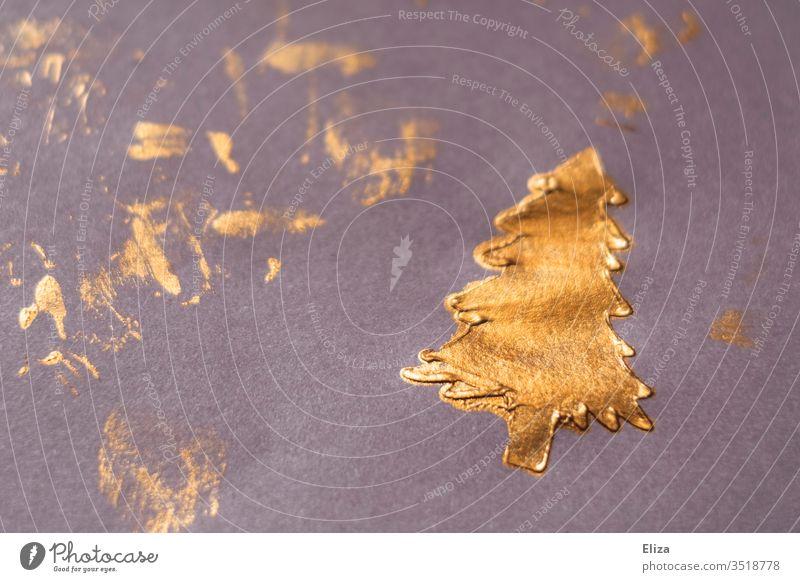 Mit goldener Farbe gemalter Weihnachtsbaum auf lila Papier. Weihnachten und Advent. basteln Christbaum weihnachtlich Tannenbaum festlich Dekoration künstlerisch