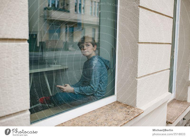 Junge sitzt einsam am Fenster und schaut auf sein Mobiltelefon während der Isolation in der Coronavirus-Epidemie Kind Einsamkeit selbstständig Fenstersims