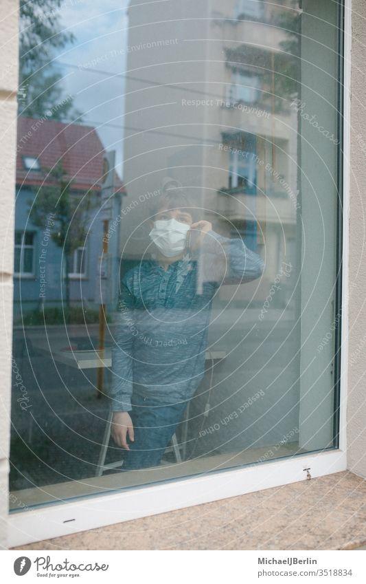 Junge mit Mund-Nasen-Schutz Maske steht am Fenster und telefoniert während Kontaktsperre durch Coronavirus Pandemie in Deutschland kind maske mund-nasen-schutz