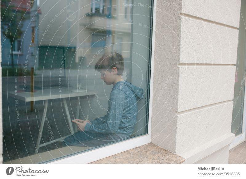 Junge sitzt einsam am Fenster und schaut auf sein Handy während Lockdown Isolation in der Coronavirus Epidemie Kind einsamkeit alleine fenster fensterbank