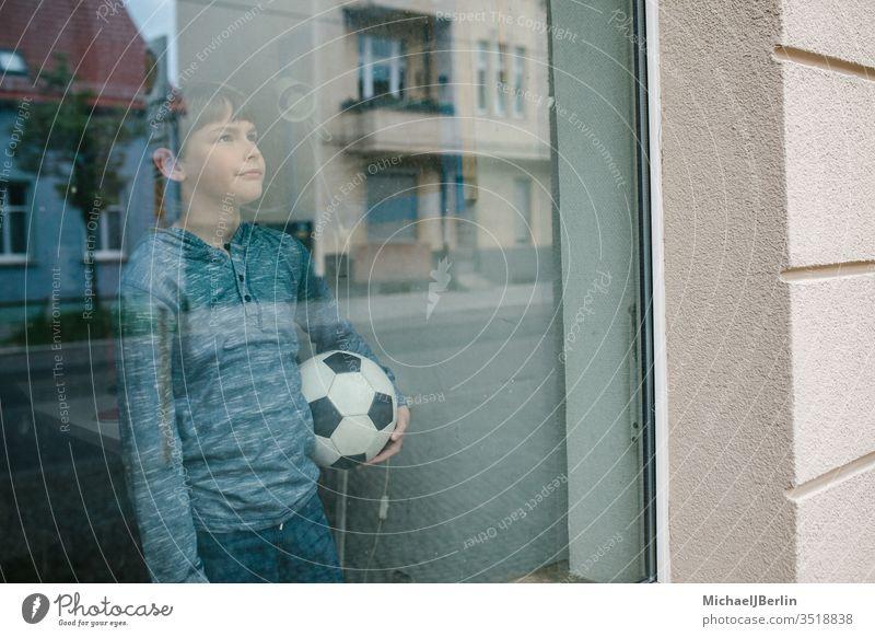 Junge steht mit Fussball am Fenster und schaut traurig nach draussen, symbolisch für Isolation von Kindern während Corona Pandemie kind junge fussball drinnen