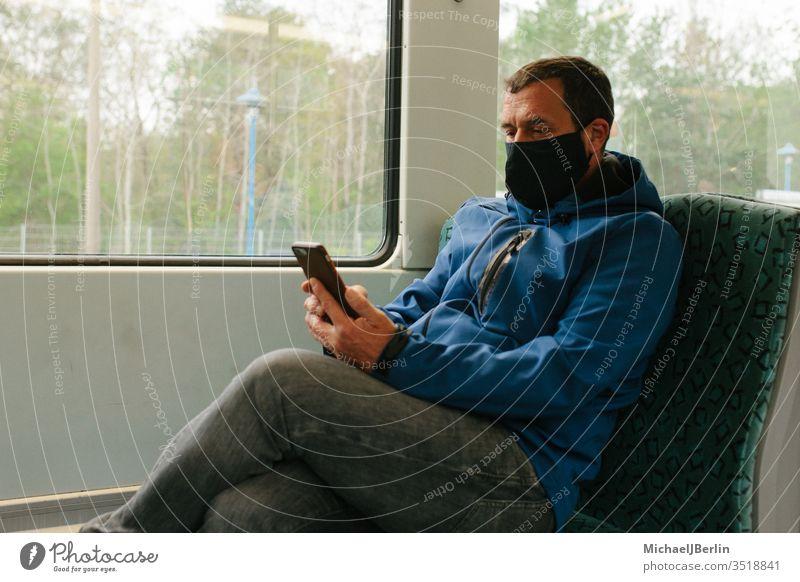 Mann mit Stoffmaske oder Mund-Nasen-Schutz im öffentlichen Verkehr während Coronavirus Pandemie Ausbruch Gesichtsmaske Maske Mund-Nasen-Maske S-Bahn Zug