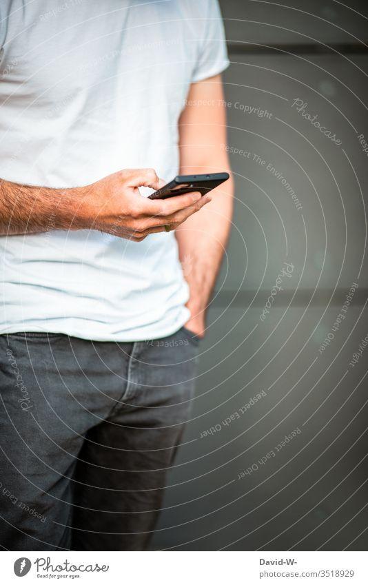 Mann benutzt sein Handy haltend Tippen Sucht suchtgefahr Informationstechnologie Internet Mobilität schreiben Nachricht Message Finger lässig Junger Mann
