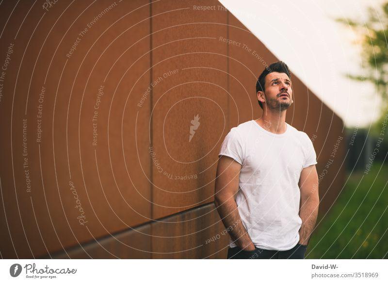 Mann mit Händen in den Hosentaschen schaut in den Himmel Blick nach oben Schatten Licht Model weißes tshirt muskeln muskolös Hoffnung Glaube Angst