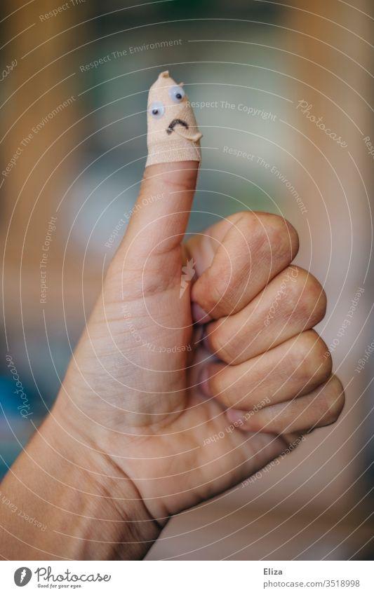 Ein Daumen der nach eine Verletzung mit einem Pflaster, auf dem ein trauriges Gesicht ist, verarztet wurde Heilung aua Heftpflaster Unfall Finger Haut verarzten