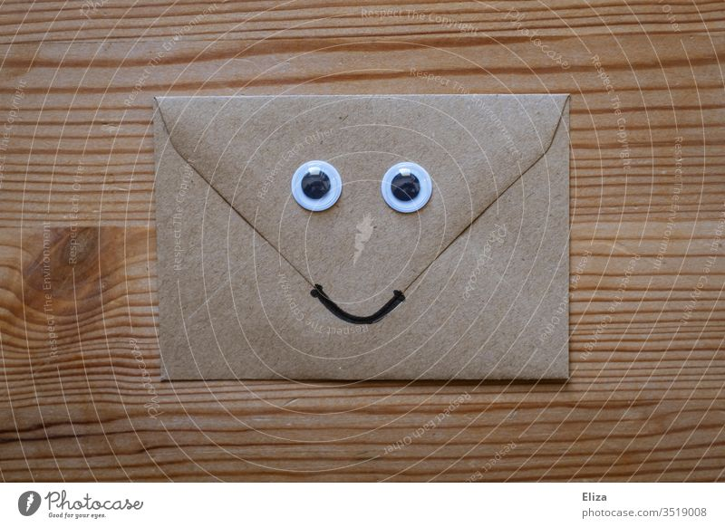 Ein freundlicher Briefumschlag mit Wackelaugen und einem lächelnden Gesicht auf Holz Augen lustig nett post erfreulich Kommunikation Nachricht Post