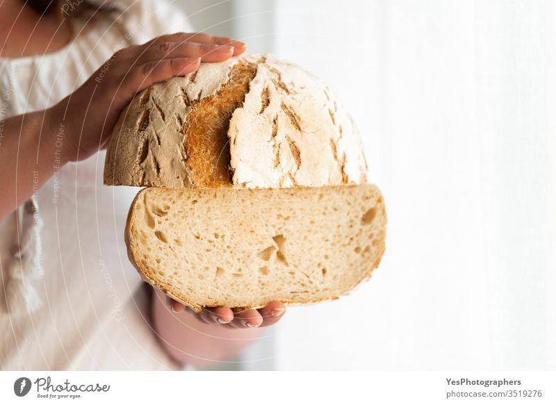 Sauerteigbrot in Händen halten. Kein Hefebrot Handwerker-Brot Backwaren Bäckerei Kohlenhydrate Konsumverhalten Kruste knusprig Fermentation Lebensmittel