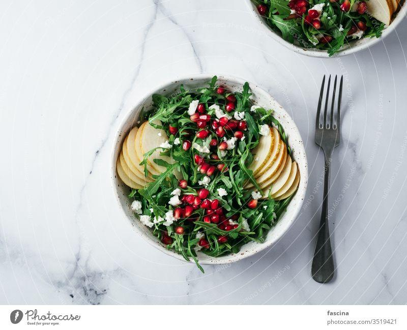 Vegane Salatschüssel mit Rucola, Birne, Granatapfel, Käse Salatbeilage Veganer Gesundheit Abendessen Lebensmittel Mahlzeit grün Vegetarier Murmel