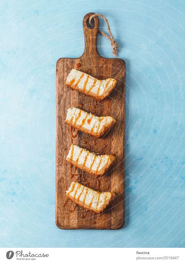 Wangenbackenstücke auf Schneidebrett über blauer Tischplatte Käsekuchen Karamell Karamell-Backenkopf karamellisiert selbstgemacht Saucen Hintergrund frisch