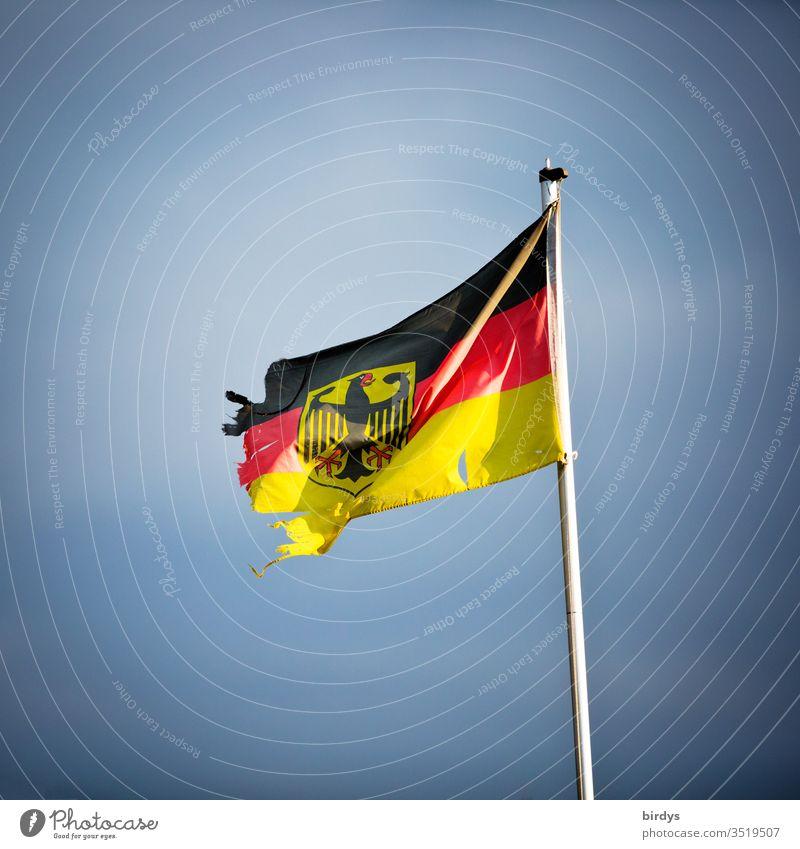 beschädigte Deutschlandfahne mit Bundesadler, Symbolbild für Instabilität und Zersetzung Deutschlandflagge Wind kaputt zerrissen Deutsche Flagge Menschenleer