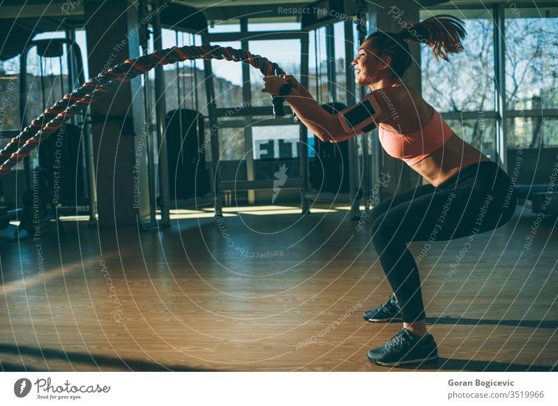 Junge Frau mit Kampfseilübung in der Fitnesshalle muskulös Stärke Athlet Fitnessstudio Seil Lifestyle Schlacht Sport passen Training Körper aktiv jung