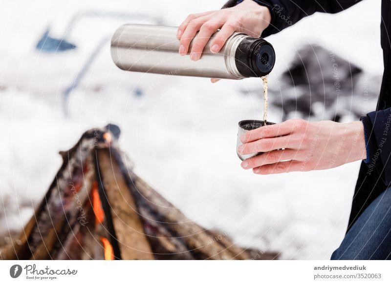 Reisende Hände Mann Nahaufnahme gießt Tee aus Fläschchen in eine Tasse im Wald in der Nähe eines Lagerfeuers. Abenteuer Herbst Camping Kaffee trinken Flasche