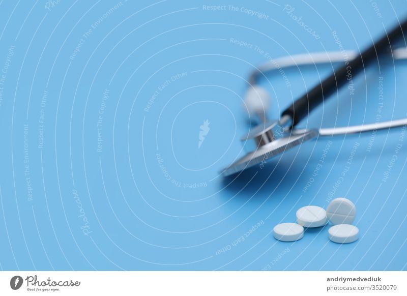 Aus der Pillenflasche auslaufende Pillen Spritzenthermometer und Stethoskop auf blauem Hintergrund. medizinisches Konzept. selektiver Fokus Behandlung Medizin