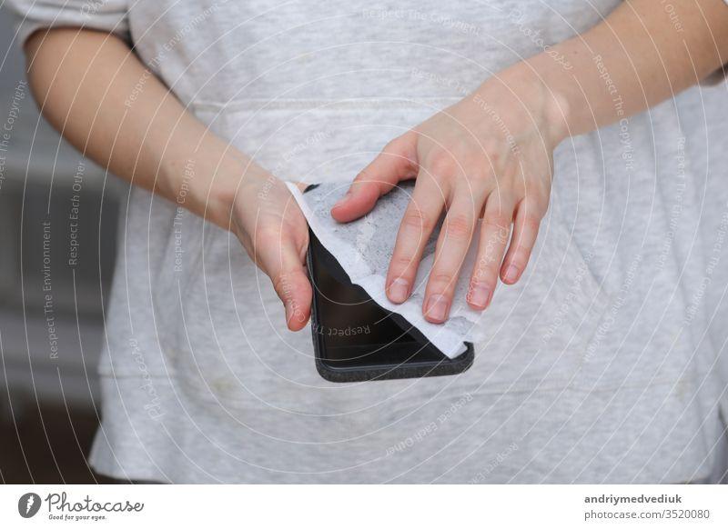 Frau desinfiziert Telefon mit antiseptischem Feuchttuch. Antiseptische Serviette zur Verhinderung der Verbreitung von Keimen, Bakterien und Coronaviren. Prävention von Coronaviren. Vorbeugung der Krankheit Coronavirus nach einem öffentlichen Ort.