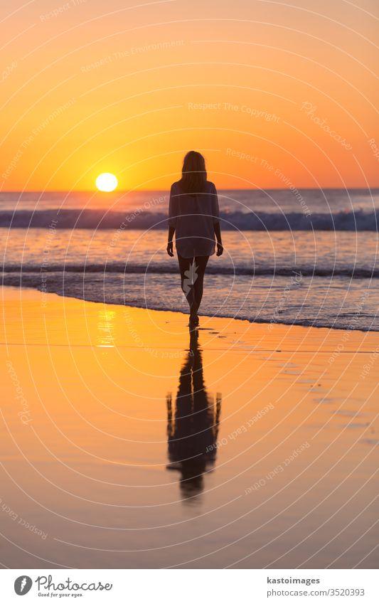 Dame beim Spaziergang am Sandstrand im Sonnenuntergang. Strand MEER Frau Sommer Fußspur Fußtritt Landschaft Küstenlinie Urlaub Wasser Natur Wellen schön Meer