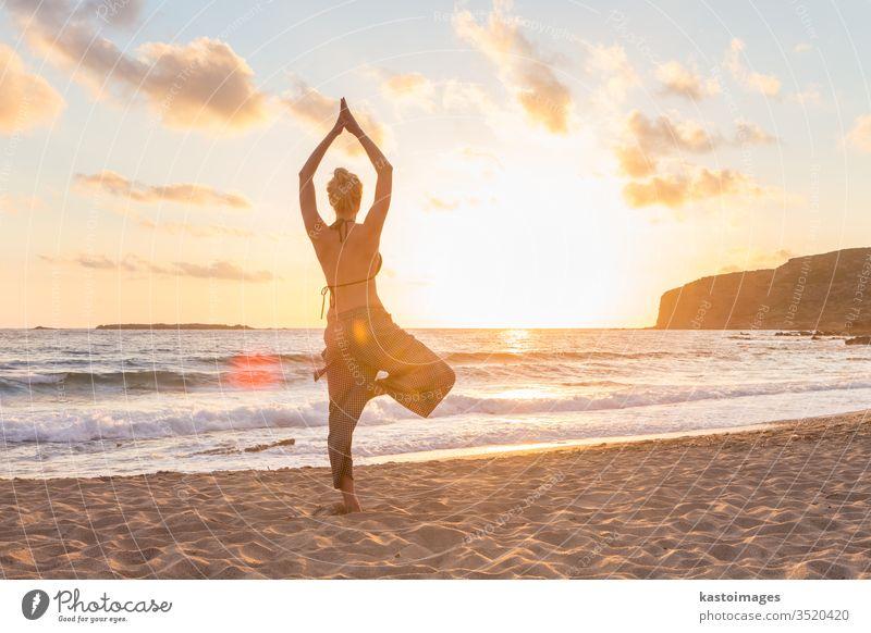 Frau, die bei Sonnenuntergang am Meeresstrand Yoga praktiziert. Strand Frieden Mädchen Körper sich[Akk] entspannen MEER Gesundheit Übung Sonnenaufgang