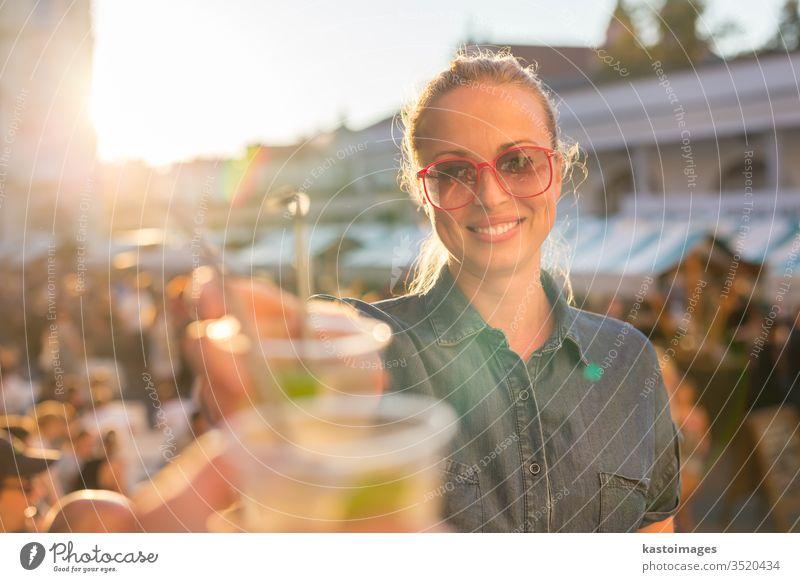Hübsches junges Mädchen stößt auf städtisches Ereignis im Freien an. Veranstaltung Stadtfest Zuprosten trinken Frau Menschen Musik Alkohol Spaß Fröhlichkeit