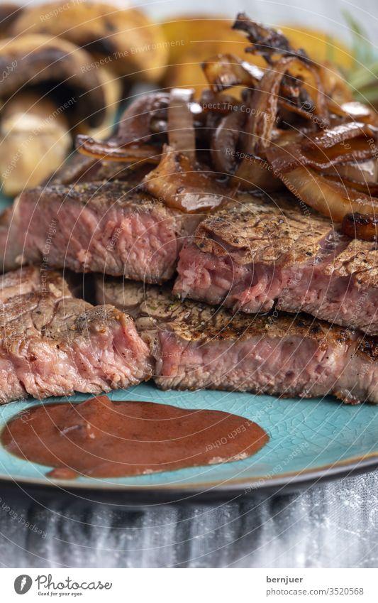 saftiges gegrilltes Steak auf dem Teller Kartoffel Champignon Pilz Rosmarin Restaurant Porterhouse Steak Filet geröstet Fleisch Tenderloin Essen Zutat Braten