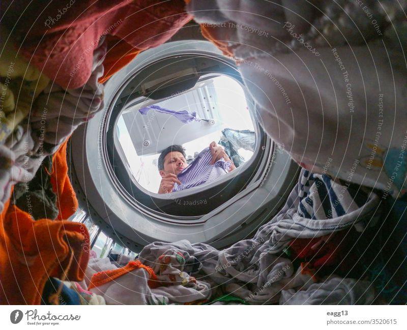 Bärtiger Mann benutzt Waschmaschine zu Hause allein Appartement Bekleidung Bachelor Vollbart tragen Arbeit Hausarbeiten Reinigen Kleidung täglich Typ