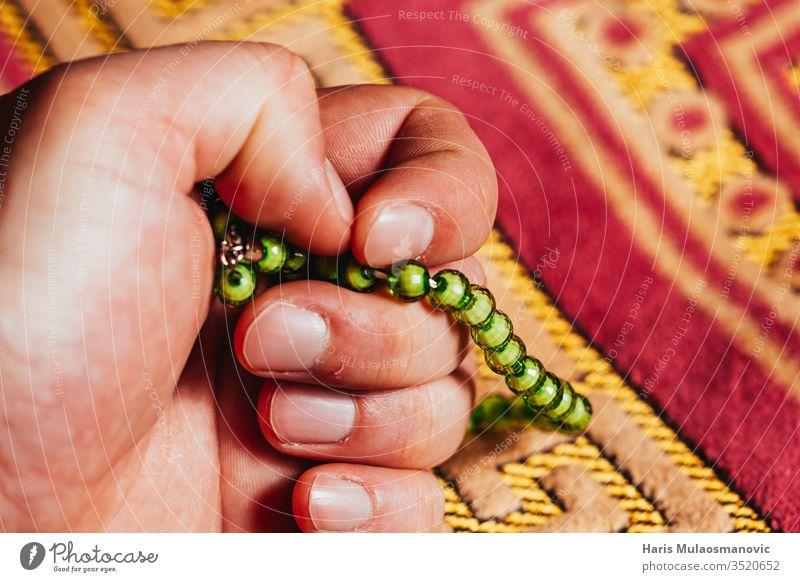 In der Hand haltender muslimischer Rosenkranz zum Mattengebet im Ramadan Kareem arabisch Kunst Hintergrund Buch Kultur Design dhikr dua Osten Glaube Fasten