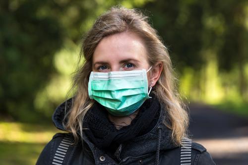 Frau mit operierter Gesichtsmaske im Freien Operation Gesichtsmaske Mundschutz Schutz covid-19 Maskenschutz Frau mit Maske Frau mit einer Operationsmaske